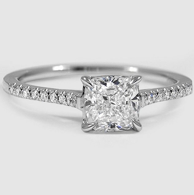 In this classically beautiful engagement ring, scalloped pavé diamonds embellish the band, which rises to a cathedral setting.