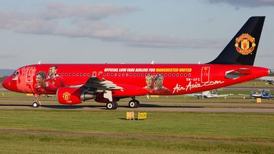 AirAsia (MY) Airbus A320-214 9M-AFC aircraft, painted in ''Manchester United'' special colours 2010, with the photos of ''Christiano Ronaldo-Wayne Rooney-Alan Smith & Ruud Van Nistelroy'' on the airframe & the badge of M.U on the tail, arriving at England Manchester International Airport in the low evening autumn light.  4/10/2007. (Manchester United F.C. or Red Devils=a professional football club founded in 14878).