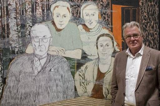 Dutch actor and artist Jeroen Krabbe poses in front of his painting   which tells the story of his grandfather Abraham Reiss, left, who was murdered in the Sobibor Nazi German extermination camp, during a press preview at the National Holocaust Museum in Amsterdam, Netherlands, Thursday, May 12, 2016. More than 70 years after tens of thousands of Dutch Jews were deported and murdered by the Nazis, the Netherlands is finally getting a national Holocaust museum.