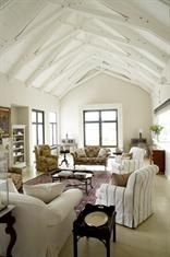 A mix of slip covered chairs and antique pieces gives a relaxed feel to this…