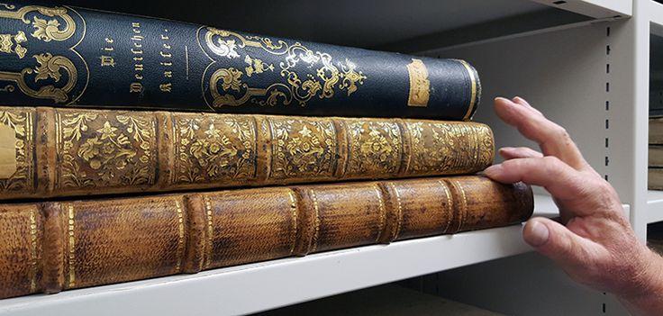 en hög med böcker liggande på en bokhylla, en hand pekar ut var en bokrygg är lagad med japanpapper