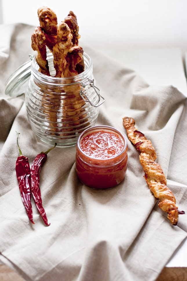 Salty bacon and cheese twists and hot tomato salsa