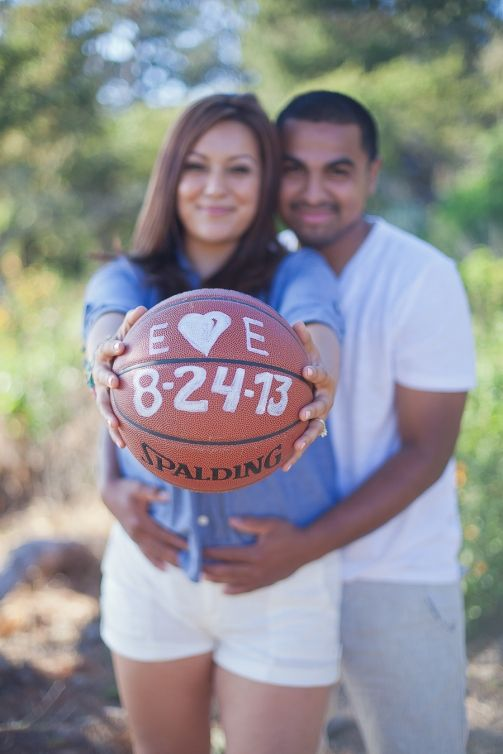 save the date- groom holding his bride and the bride is holding up a basketball with their first initials and the date on it - For the sports loving couple