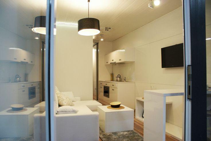 Widok na wnętrze Rubiloft z zewnątrz przez otwarte drzwi, które są w całości przeszkolene tak samo jak cała ściana salonu.