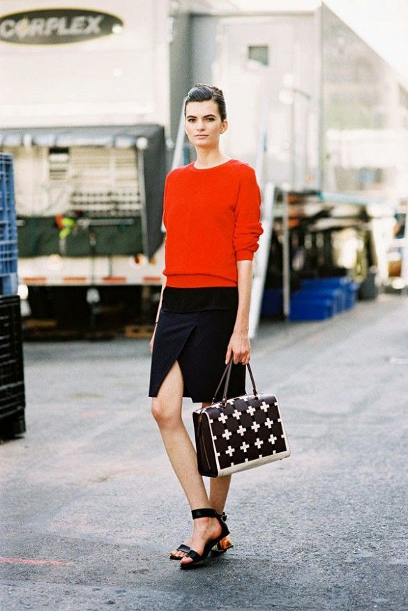 A red sweater is worn with a black slit skirt, heeled sandals, and a structured printed bag.