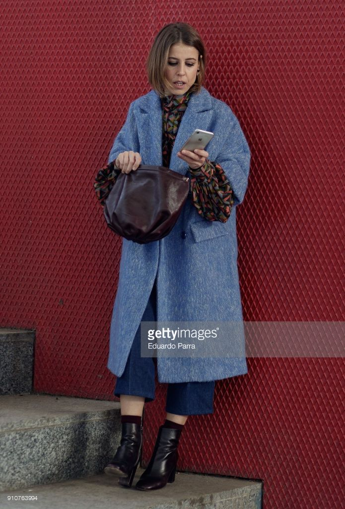 Actress Ruth Llopis wears a Ailanto coat and shirt, a vintage pants, Bimba y Lola ankle boots and Zara handbag during the Mercedes Benz Fashion Week Autumn/Winter 2018-19 at Ifema on January 26, 2018 in Madrid, Spain.
