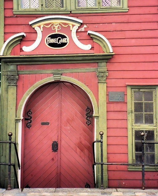 Coral painted diagonal wood double arched doors with scroll black metal hardware and an interesting wood arch!