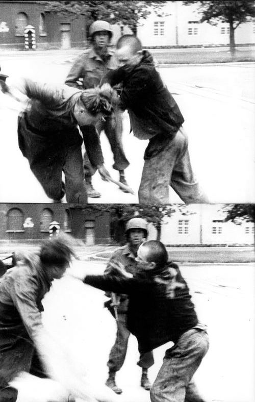 A freed prisoner beating a German camp guard at the liberated Dachau Concentration Camp in 1945.