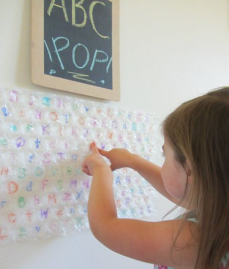 ABC Pop! | Parents | Scholastic.com : Using large bubble wrap and colorful permanent markers, write upper and lower case letters on the backside of the wrapping. Turn the plastic over and let it dry. Next, tack or tape (painter's tape) the activity to a wall. Call out letters to your toddler and have him or her pop every instance of the letter. This activity helps develop letter recognition.