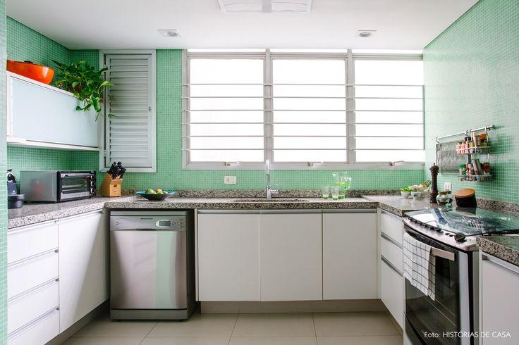 Cozinha com bancada de granito e parede revestida com pastilhas na cor verde.