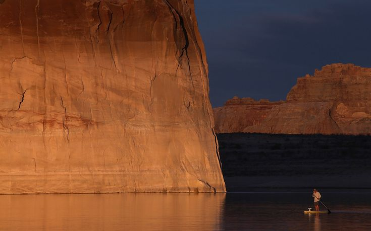 A paddleboarder floats by Lone rock on Lake Powell near Big Water, Utah. As severe drought grips parts of the Western United States, a below average flow of water is expected to flow through the Colorado River Basin into two of its biggest reservoirs, Lake Powell and Lake Mead.