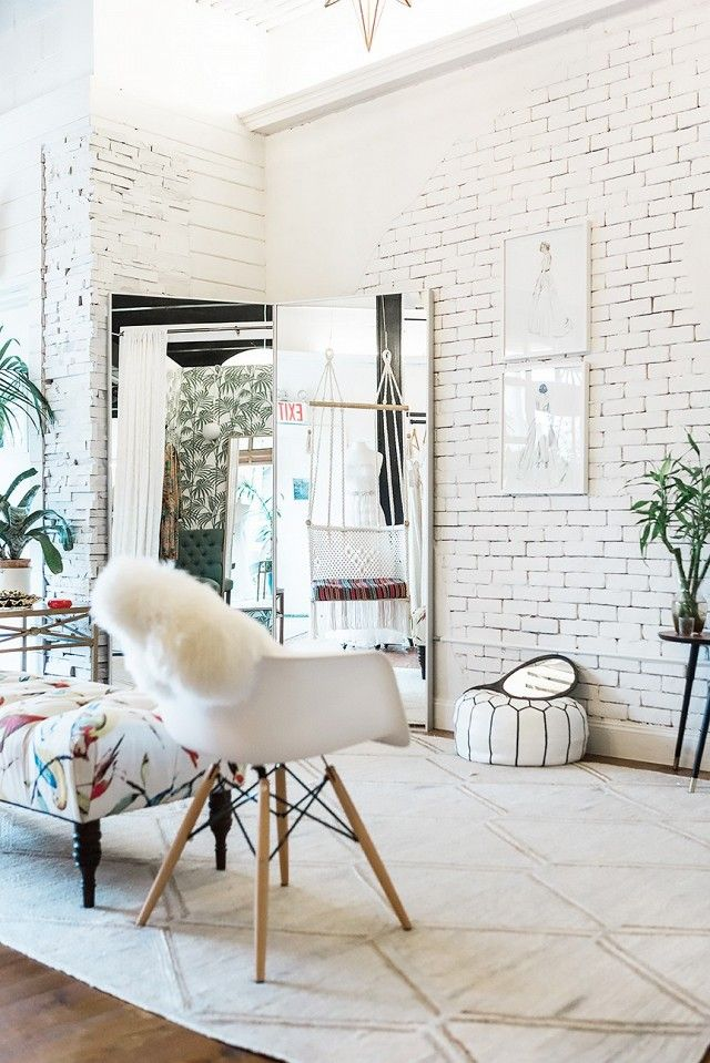 Elegant retail space with white washed bricks and a large mirror propped up on the floor