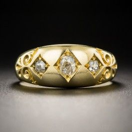 From early twentieth century Birmingham, England, crafted in rich 18ct. gold, a late-Victorian classic featuring a vibrant trio of diamond-set diamonds book-ended by fanciful hand engraving. Three bright white and sparkling old mine-cut diamonds total a quarter-carat. Currently ring size 6 1/2. Circa 1902.
