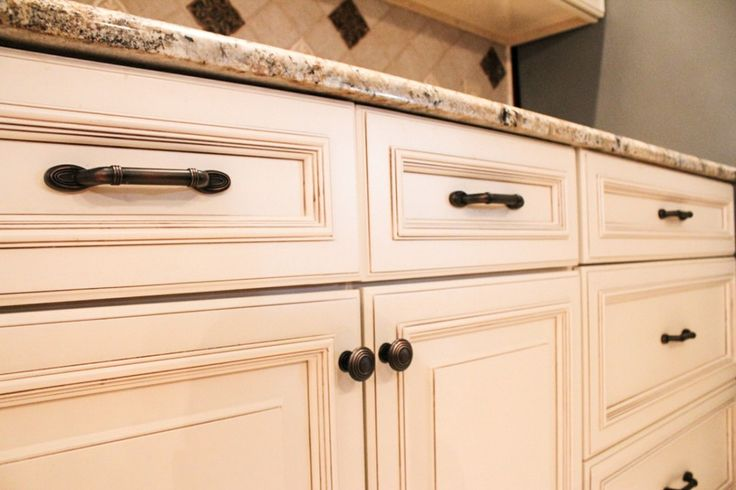 Ivory paint with a glaze, we have dark bronze hardware in both knobs and handles paired to accentuate the glaze on the cabinets and well as the decorative inset backsplash tiles.