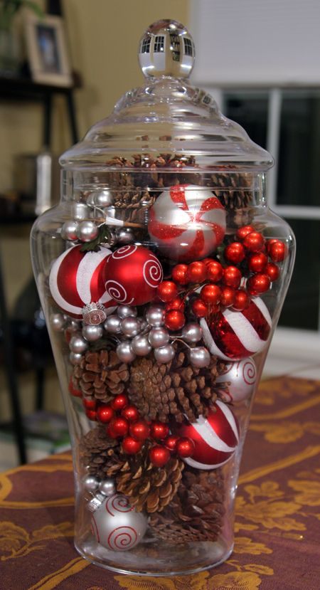 easy holiday centerpiece made from a glass jar filled with festive ornaments, fake berries, and pine cones.