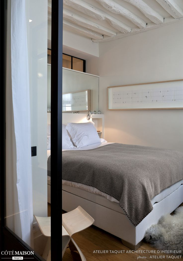 Chambre à coucher immaculée avec ses poutres apparentes