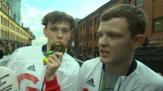 Image copyright                  Sky News                  Image caption                                      The mystery blaggers were dressed in Team GB tracksuits and wore plastic medals around their necks                                Two imposters sneaked on to a float during the celebratory Rio 2016 parade in Manchester, the British Olympic Association (B