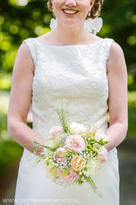 Bruidsboeket in zachte roze en crème pasteltinten met gipskruid.