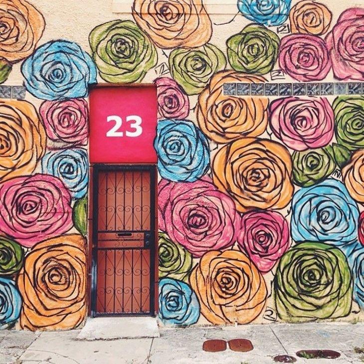 Miami, EUA - Casa con decoración de rosas alrededor de una puerta con barandal negro y un número 23 en un fondo rosa