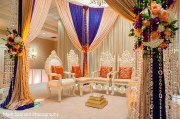 Orange and puple mandap with regal white chairs. Find more Indian wedding decor inspirations at #www.jivaana.com. #shop #inspirations #weddingvendors #indianfestivals