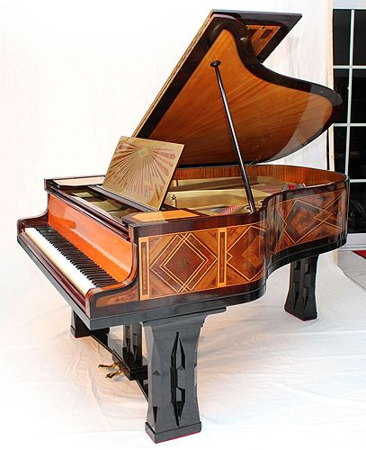 A 1900, art cased Schiedmayer grand piano with an Art-Deco case inlaid with mother of pearl, lapis lazuli and malachite in geometric designs. The lid design resembles an angels wing. Music desk made from brass with a sunburst design. Legs feature geometric square pillar design this is also echoed in the piano lyre. This Schiedmayer piano was designed by Peter Behrens. #Behrenspiano #artcasedpiano #uniquepiano