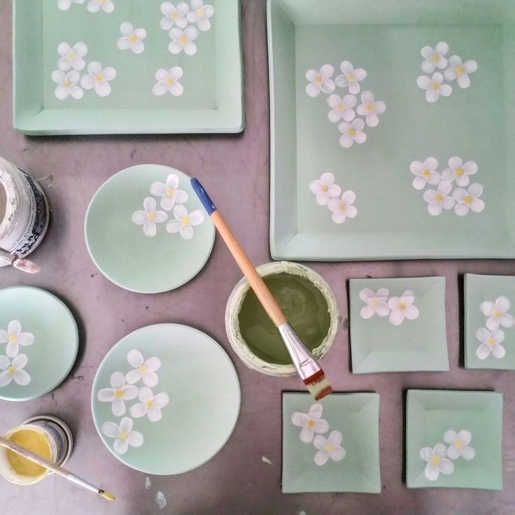 Applying underglaze to plates and painting dogwood flowers on top.