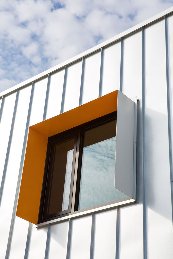 Designshop has added orange accents to the protruding window shades of this house in Tennessee