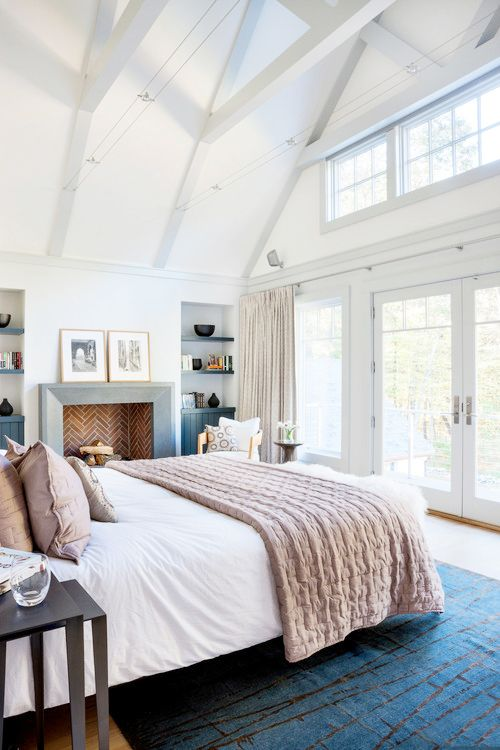 LDa Architecture & Interiors serene and light filled bedroom. With high beams, windows, and a cozy fireplace this is a bedroom we all want to sleep in.