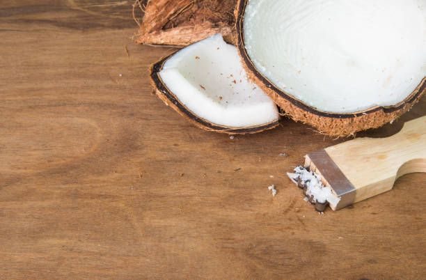 coconut and coconut grater on wooden background