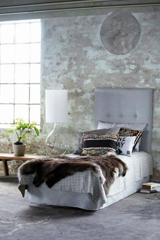 Upholstered bedhead against rough concrete wall.