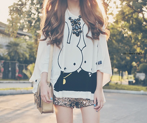 oversized graphic shirt, sparkly gold shorts, black gems necklace, and goldish color bag.