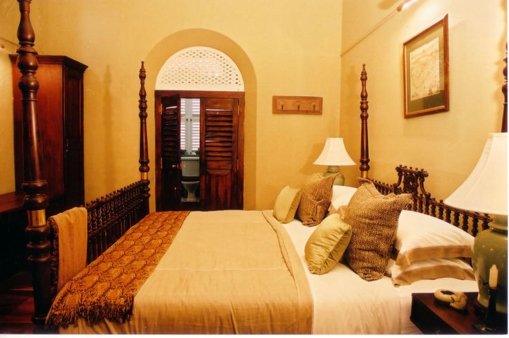 This bedroom emits a colonial feel with the use of dark wood and golden colours.