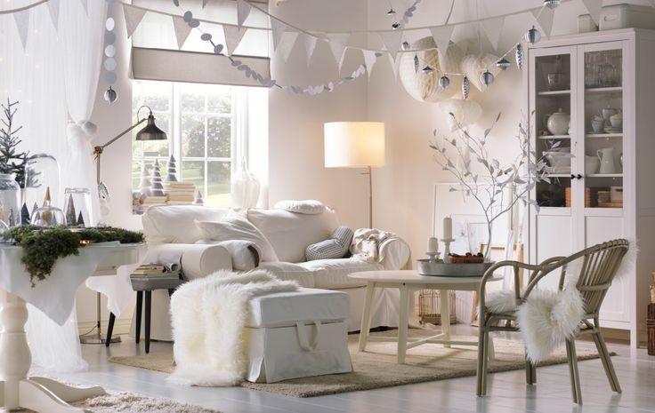 Soggiorno nei toni del bianco, con decorazioni appese ed elementi naturali ispirati al Natale.