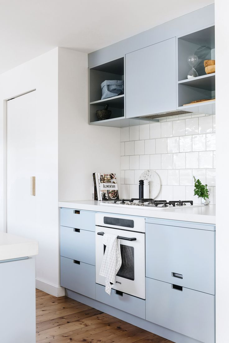 A blue and white galley-kitchen creates a functional space that is separate but connected to the nearby living areas in this renovated Edwardian Melbourne home. Photography: Emily Weaving | Styling: Ruth Welsby | Story: Australian House & Garden