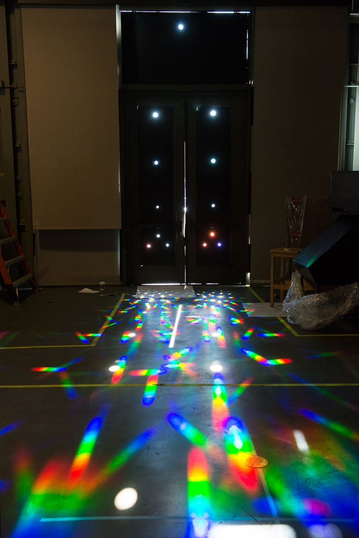 Exploratorium: These rainbow prisms were created by blocking the light on two glass doors with big paper, cutting out holes, and then placing diffraction grating over the holes