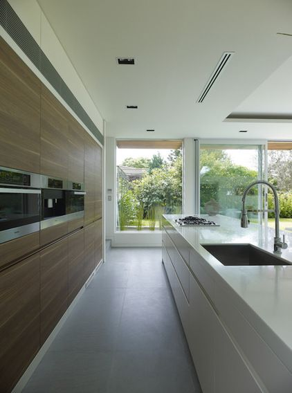 Neutral stone colour bench tops steer attention away from a large island bench and direct it towards the main wall behind