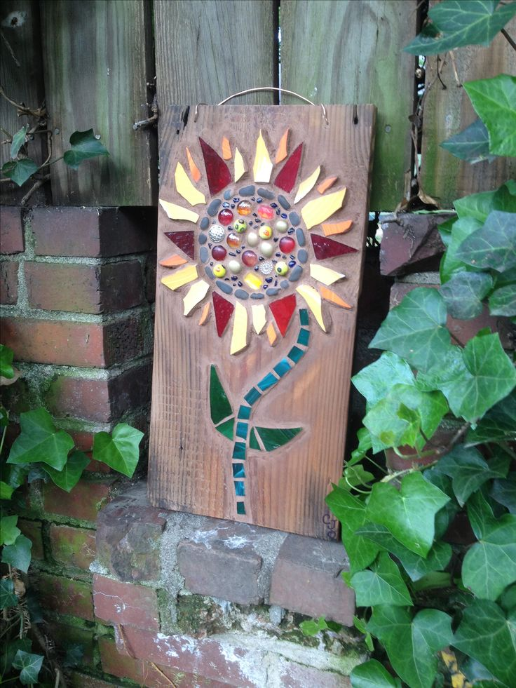 """""""My latest piece! Sunflower made from broken china, stained glass pieces, buttons, beads and other trinkets mounted on reclaimed wood."""" By Carla O'Brian"""