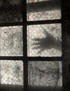 Handen : Schaduw van een uitgestrekte hand schijnt door een raam met hek ervoor.…