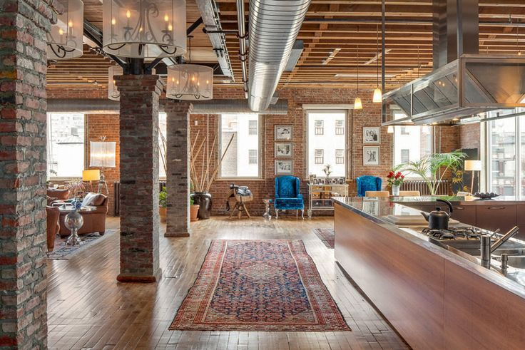 This NYC loft has hardwood floors, exposed brick, open ductwork, exposed ceiling rafters, stan-alone columns, stainless steel kitchen counters, leather chairs and an oriental runner rug.