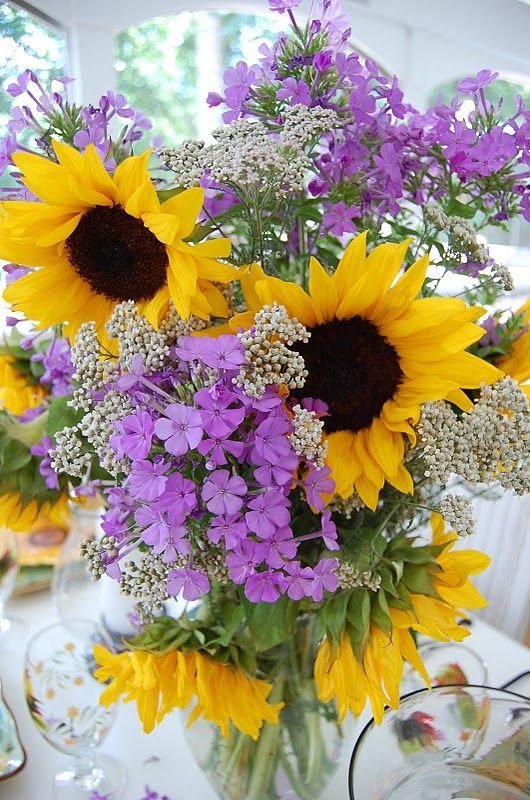 Sunflowers!  Don't know what the tiny white flowers are but they are perfect in this arrangement.  Just love it.