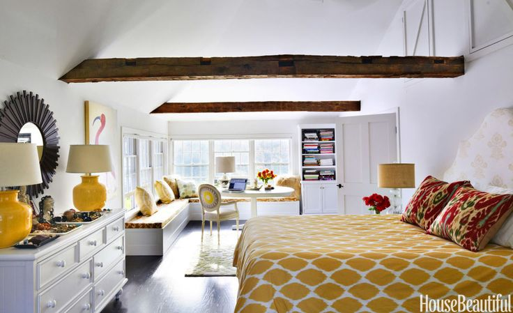 In Susanna Salk's Connecticut lake house, vintage beams accentuate the bedroom's soaring ceiling.