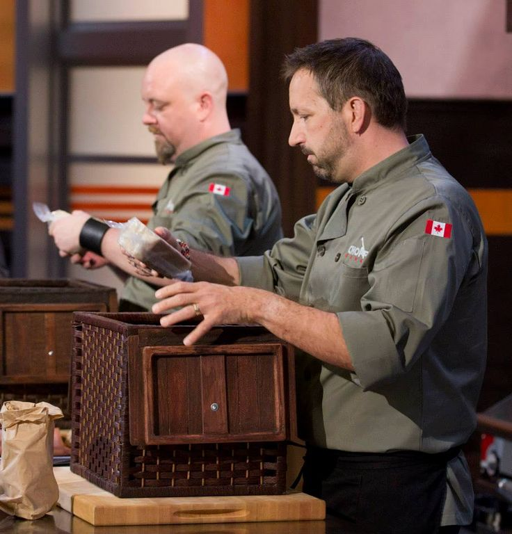 Chef Stuart and Chef Dez carefully inspect the contents of their mystery baskets.