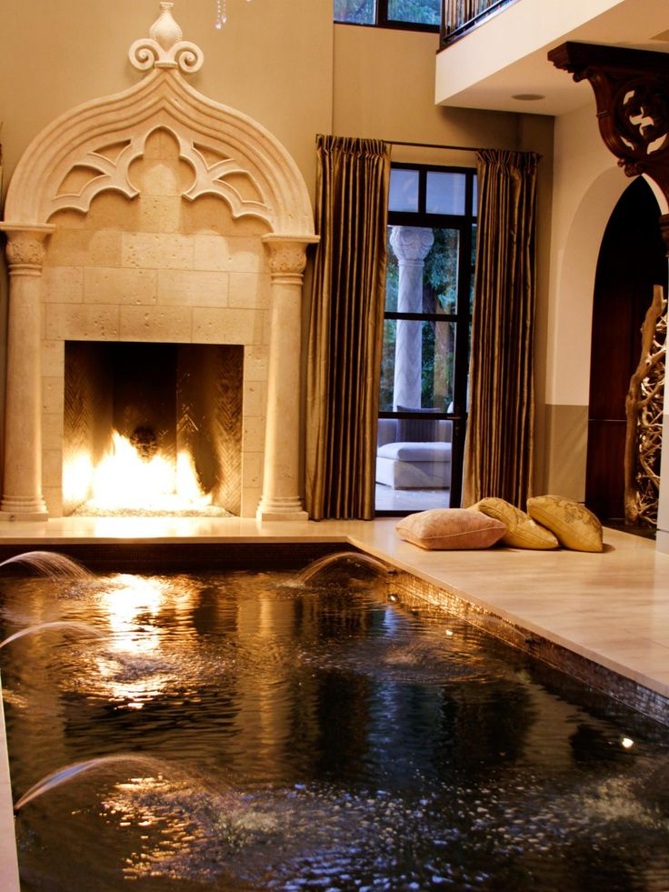 Fire light dances on the surface of this indoor spa. Water fountains and ornate stone molding add more luxurious touches to this already over-the-top retreat.