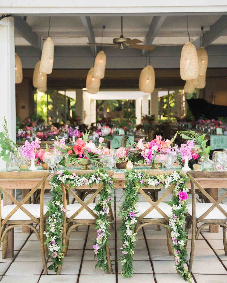 A Casual Beach Wedding in Puako, Hawaii | Martha Stewart Weddings - Grace Flowers Hawaii made the sweetheart chair garlands and centerpieces with locally sourced flowers and variegated leaves. The setting had a relaxed and beachy appearance, since the design was inspired by the natural green, pink, red, and orange colors of Hawaii. #weddingflowers #weddingideas #beachwedding #tropicalwedding