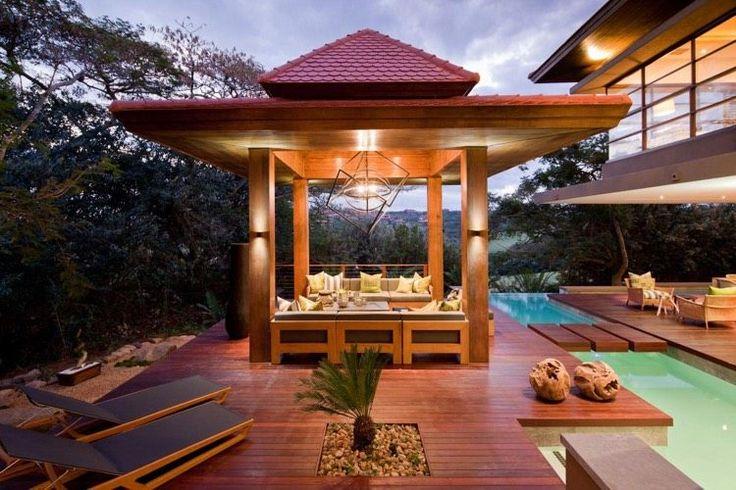 aménagement de jardin cosy - une belle terrasse en bois dotée d'un gazebo en bois, un salon de jardin moderne et un éclairage d'ambiance