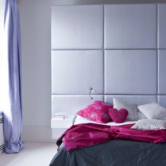 The impressive large head board upholstered on plain lilac fabric makes a statement in this modern bedroom / El enorme cabecero tapizado en tila lisa de color lila es la decoración principal de este dormitorio moderno