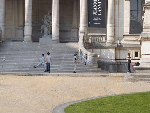 Foot chorégraphie : Cette photo tient pour partie de la chance, mais j'avoue avoir guetté l'instant qu'il fallait.  Je pars en retard du boulot, toujours quelque chose à finir, un dernier client à servir, attrape un sandwich à la bonne boulangerie, et le mange en marchant vers Alma-Marceau. Au travers des grilles du parc, à hauteur du Palais de Tokyo mais de l'autre côté, ces enfants qui jouaient.  [Paris XVIème, m