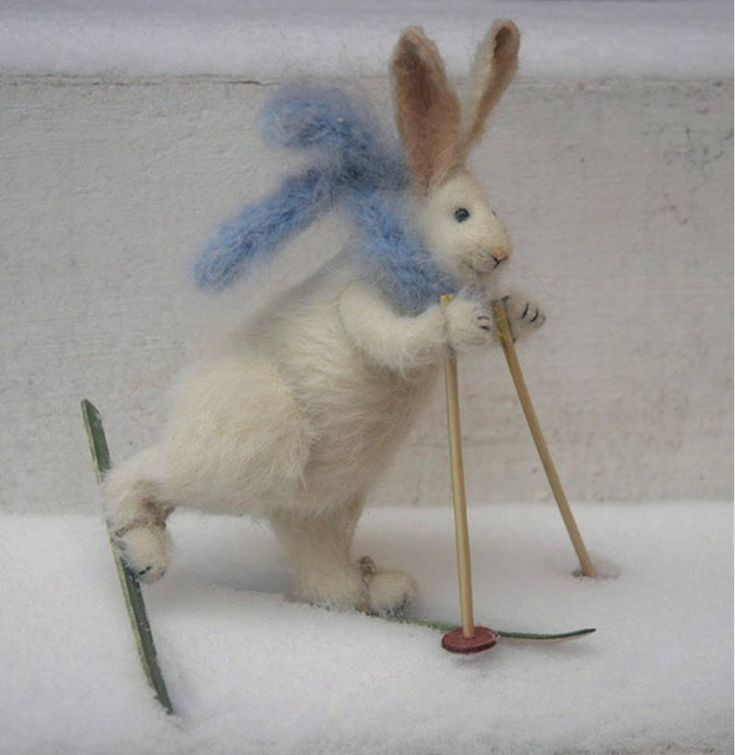 This 'Skiing Rabbit' is the work of textile artist Natasha Fadeeva. Natasha creates her little creatures by knitting them from mohair, fabricating from fabric, and creating a few from needle felted wool. She embellishes her creations with embroidery, beads and other accessories.  See more of Natasha's work on her website at http://www.fadeeva.com/#