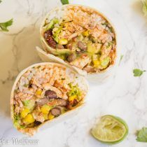 These spicy chipotle chicken burritos are stuffed with cilantro lime rice, chipotle chicken, guacamole, salsa, black beans, and corn in a large tortilla.