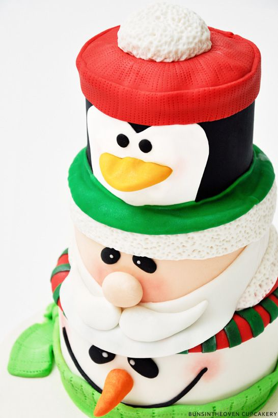 Inspired by a stack of Christmas cookie tins... this Santa, Penguin, Snowman Cake will have you squealing! An adorable Christmas cake by BunsInTheOven Cupcakery.